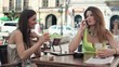 Two happy pretty girlfriends talking on cellphone in cafe