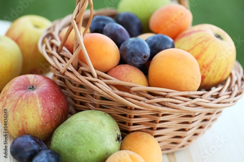 Basket filled with apples, pears, apricots and plums.
