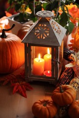 Lantern with candles, pumpkins and autumn decorations.