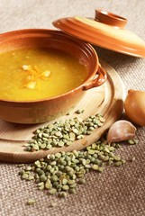 Pea soup with carrot and bacon in pot.