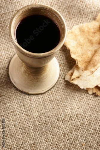 Chalice with wine and piece of bread on fabric background