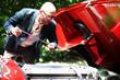 Mann überprüft Ölstand beim Auto