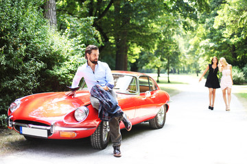 Mann und Frauen mit Sportwagen