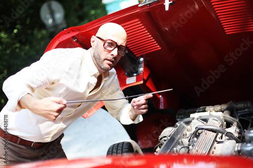 Mann übwerprüft Ölstand beim Auto