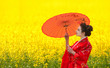 Asian style portrait of woman with red umbrella in yellow field