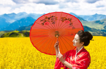 Woman with red Chinese umbrella in yellow field