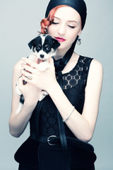 Beautiful woman with a puppy in her arms.