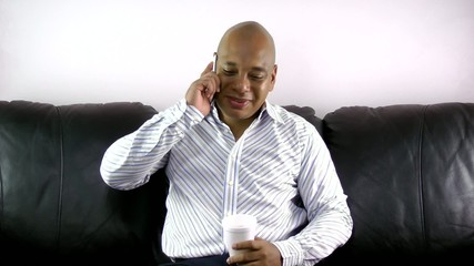 African man drinking while talking on phone