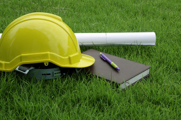 Engineer hat and books in the field.