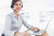 Smiling call centre agent working at desk