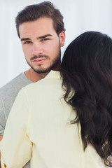 Woman giving hug to unsmiling boyfriend