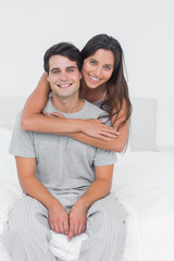 Woman embracing her partner sat in bed