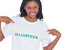 Smiling young woman wearing volunteer tshirt and pointing to it