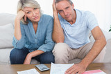Anxious couple going over bills looking at camera