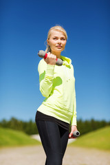 sporty woman with light dumbbells outdoors