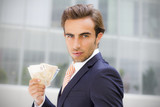 Young businessman outside office holding banknotes