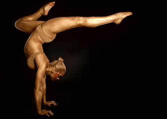 acrobat dancer toned in gold  posing over black background