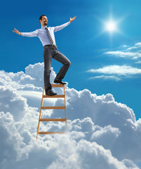 businessman with open arms standing at the top of ladder