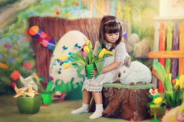 Easter composition of a little girl in a white dress with a rabb
