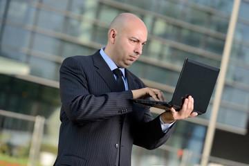 Manager con computer portatile in esterni