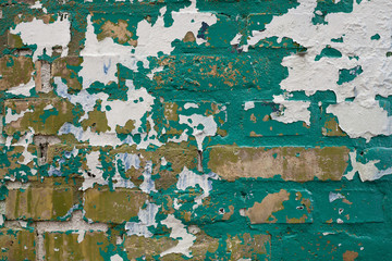 Green and White Paint Peeling off Yellow Brick Wall