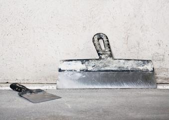 Masonry trowels near a grey plaster wall