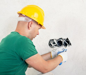 electrician with knife cutting a wire