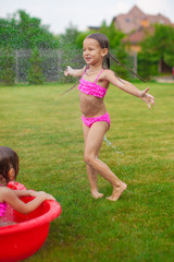 Adorable little girl in a swimsuit playing and splashing in the