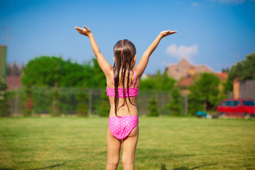 Back view of little girl in a swimsuit playing and splashing in