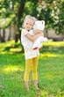 Little girl portrait in a park - holding toy bear