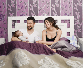 Happy parents in bedroom with baby