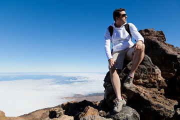 Young Man Having a Rest in a High Peak Over Clouds