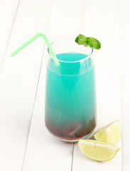 Glass of multicolor cocktail on white background