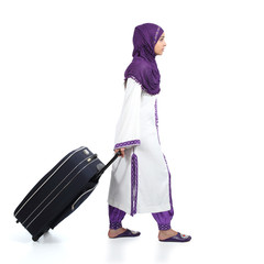 Muslim immigrant woman walking carrying a suitcase