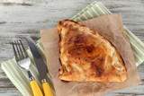 Pizza calzone on tracing paper  on napkin on wooden table