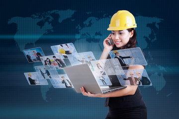 Attractive contractor calling and looking at digital photos