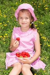 Cute girl eating strawberries