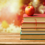 Old vintage books and apple over autumn leaves bokeh background