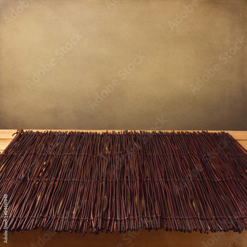 Bamboo tablecloth on wooden table over grunge background