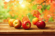 Apples on woodn table over autumn bokeh background