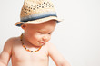 Kleinkind mit Halskette und Hut