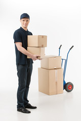 Moving boxes. Full length of young deliveryman holding a stack o