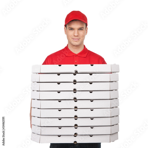 Your pizza! Young cheerful pizza man holding a stack of pizza bo