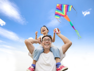 happy little girl on his father shoulder with colorful kite