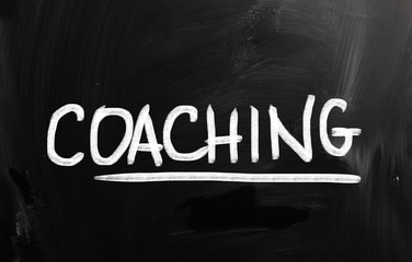 """Coaching"" handwritten with chalk on a blackboard"