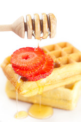 Belgian waffles and strawberries on a plate, stick for honey and