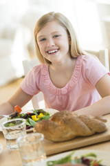 Girl Having Meal At Dining Table