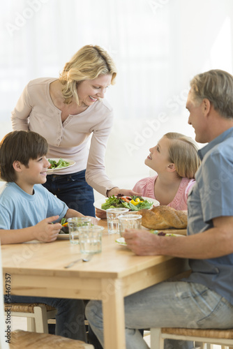 Woman Serving Food To Daughter At Dining Table