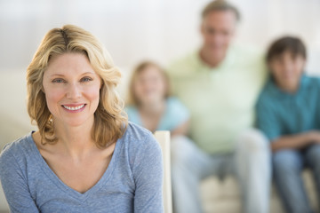 Woman With Family Sitting On Sofa In Background At Home