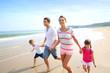 Happy family running on the beach